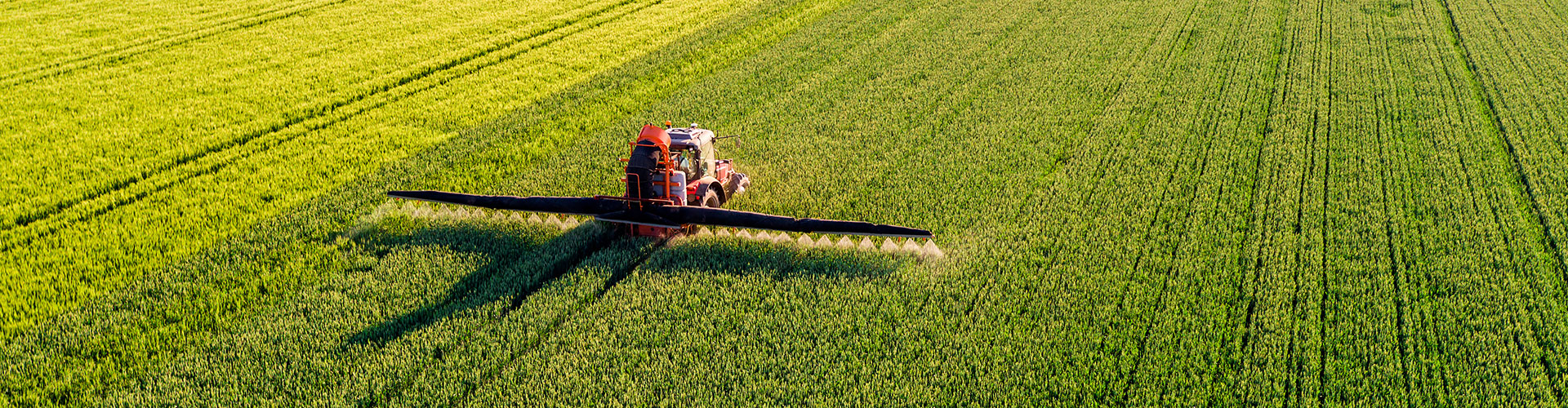 Agricultural sprayer driving through field